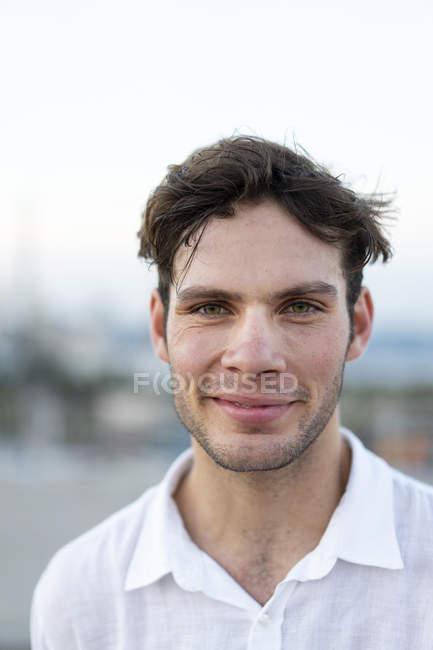 Ritratto di giovane uomo sorridente con capelli arruffati all'aperto — Foto stock