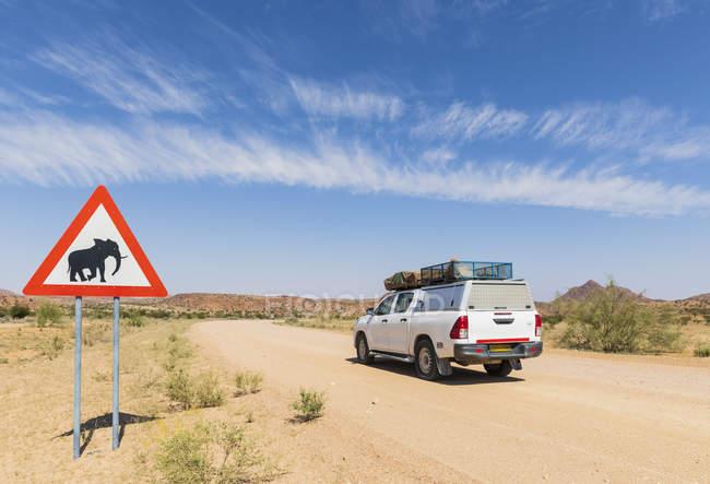 Namíbia, Região de Erongo, veículo off-road em pista de areia, sinal de cruzamento de veados com elefante — Fotografia de Stock