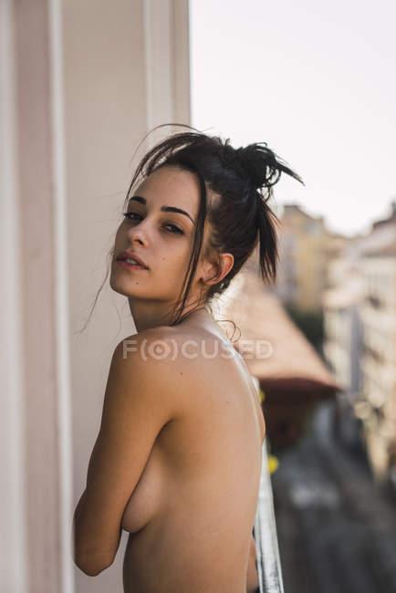 Retrato de sensual sem camisa jovem posando na varanda acima da cidade — Fotografia de Stock