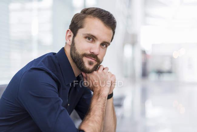 Ritratto di giovane uomo d'affari sicuro seduto in sala d'attesa — Foto stock