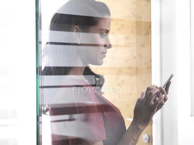 Profile of woman behind glass pane using smartphone — Fotografia de Stock