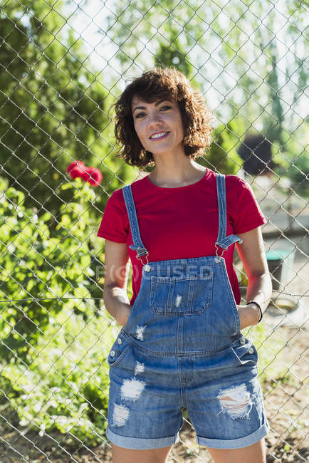 Portrait of smiling woman wearing denim dungarees in nature — Stock Photo