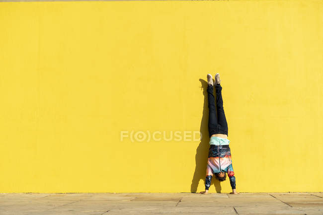 Acrobat doing handstand in front of a yellow wall — Stock Photo
