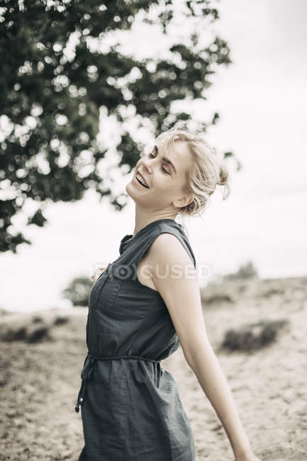 Portrait of smiling young woman relaxing in nature and wearing casual dress, dancing with closed eyes — Stock Photo