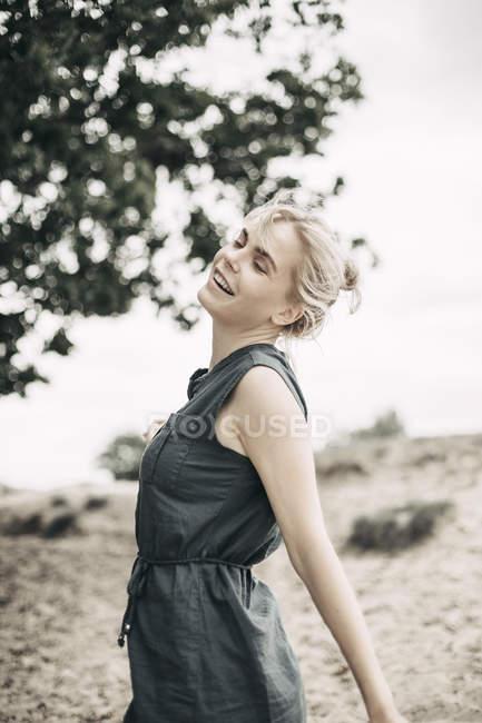 Портрет усміхнена молода жінка розслабляє в природі і носить повсякденний одяг, танці з закритими очима — стокове фото