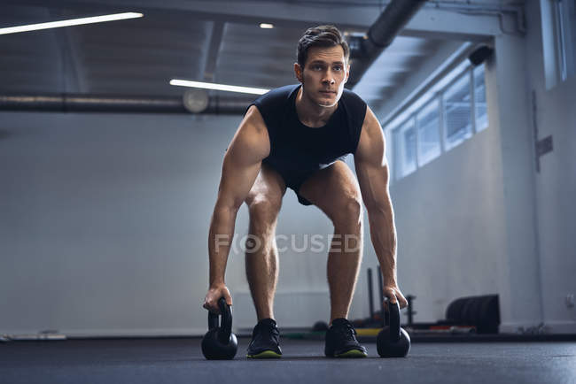 Man doing kettlebell exercise at gym — Stock Photo