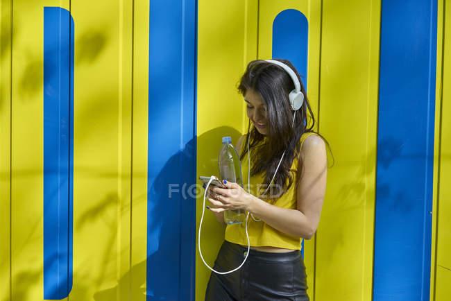 Молодая женщина слушает музыку с наушниками и текстовые сообщения бутылки с водой — стоковое фото