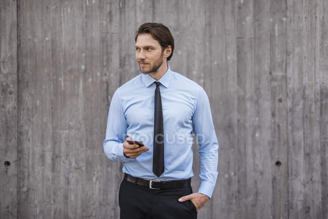 Homme d'affaires debout au mur de béton tenant smartphone — Photo de stock