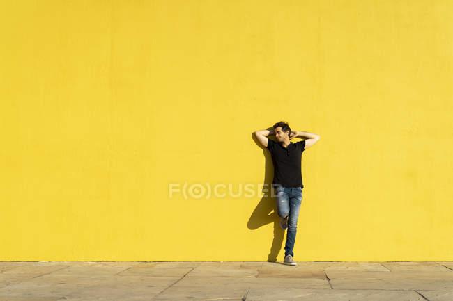 Людина, спираючись на жовту стіну з руками позаду голови — стокове фото
