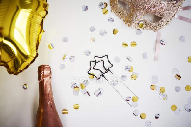 Маскировать бутылку шампанского и конфетти на белом фоне, после концепции вечеринки — стоковое фото