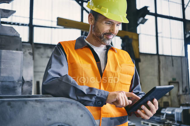 Smiling man wearing protective workwear using tablet in factory — Stock Photo