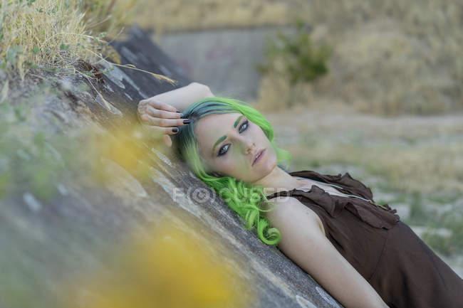 Портрет молодой женщины с окрашенными зелеными волосами и бровями в природе — стоковое фото