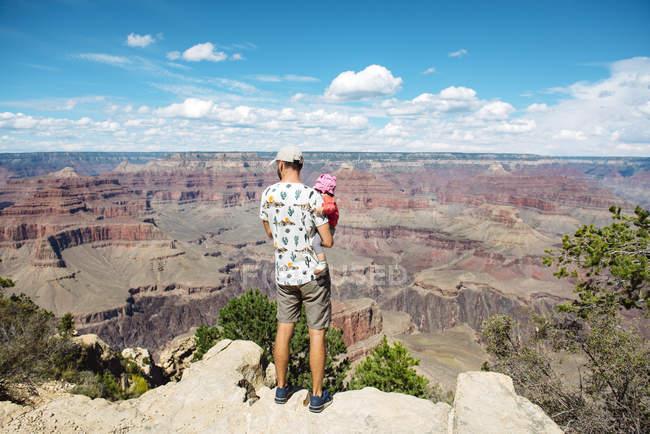 Estados Unidos, Arizona, Parque Nacional del Gran Cañón, padre y niña disfrutando de la vista, vista trasera - foto de stock
