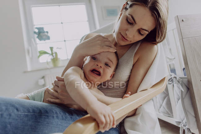 Mother cuddling and playing with baby son at home — Stock Photo