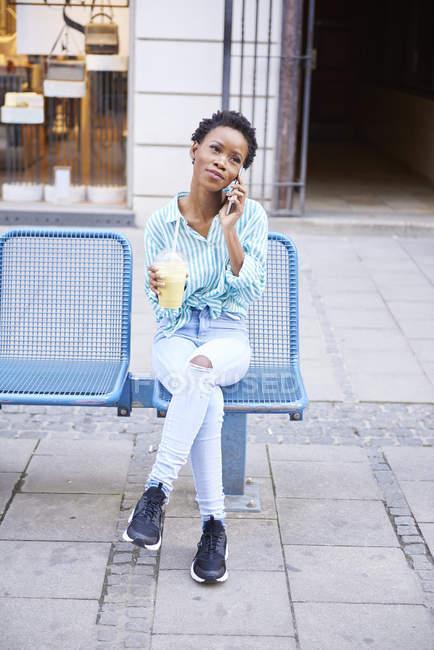 Retrato de mujer en el teléfono sentado en la ciudad con batido - foto de stock