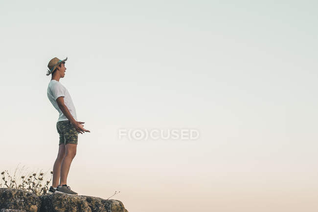 Giovane uomo in piedi sulla roccia, urlando di gioia — Foto stock