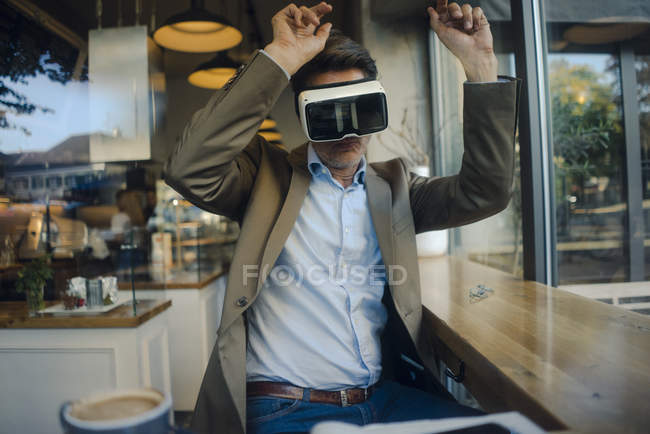 Mature businessman sitting in coffee shop, looking through VR glasses, dancing — Stock Photo