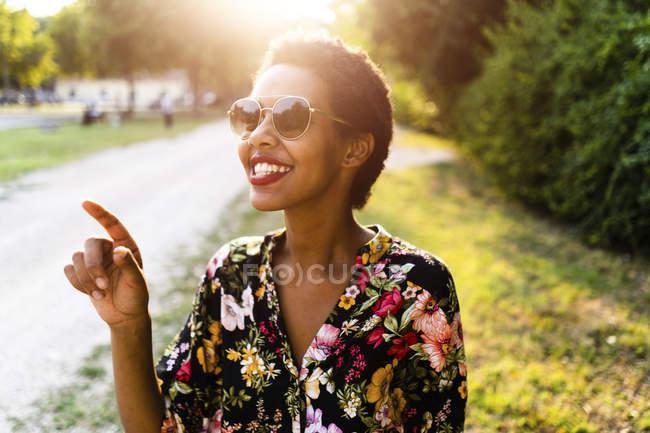 Joyeux jeune femme portant des lunettes de soleil à l'extérieur au coucher du soleil — Photo de stock