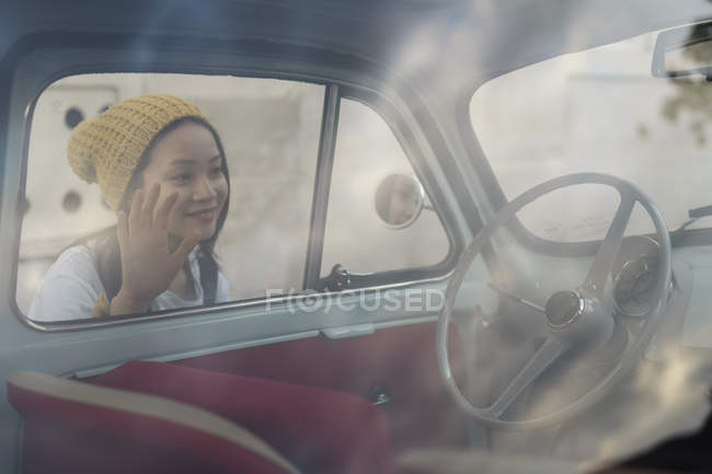 Young woman looking into small vintage car — Stock Photo