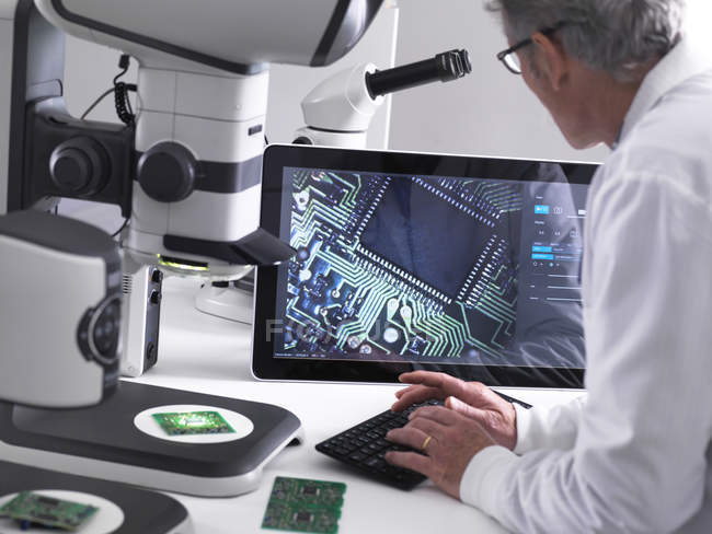 Engineer using a 3d stereo microscope for quality control in the manufacturing of circuit boards for the electronics industry — Stock Photo