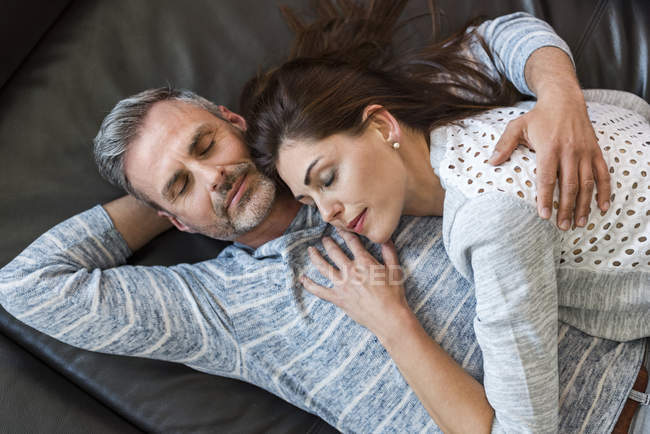 Relaxed couple lying on couch at home — Stock Photo