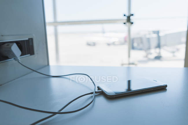 Charging smartphone at airport — Stock Photo