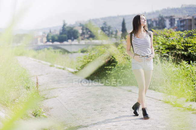 Усміхнена молода жінка, яка ходить по сільській стежці влітку — стокове фото