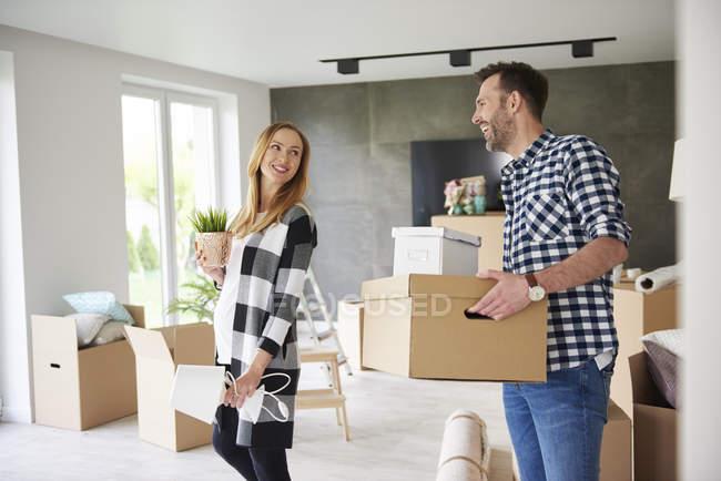 Coppia felice trasloco che trasporta scatola di cartone e pianta — Foto stock
