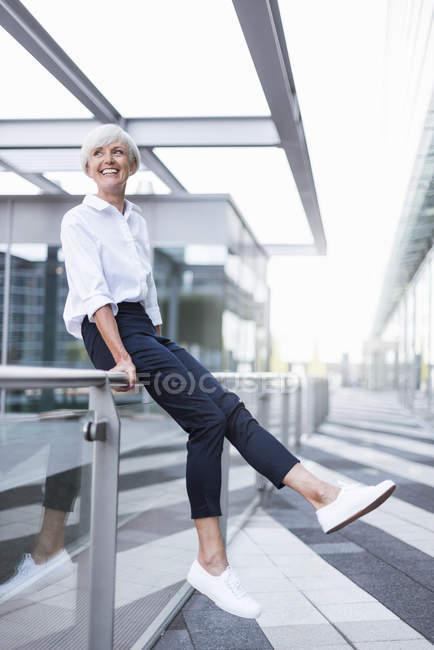 Heureuse femme âgée assise sur une rampe en ville et regardant autour — Photo de stock