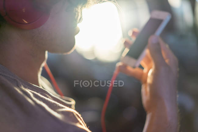 Young man in plane with cell phone and headphones — Stock Photo