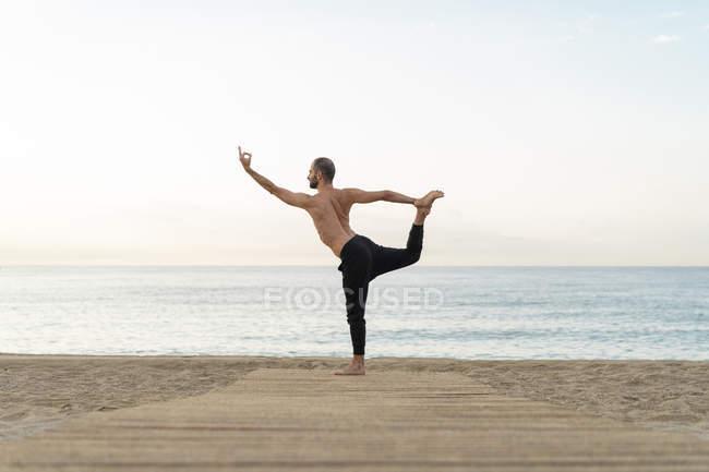 Spanien. Mann macht abends Yoga am Strand, Tänzerposition — Stockfoto