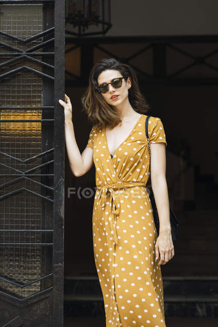 Portrait of attractive woman wearing yellow dress with polka dots — Stock Photo