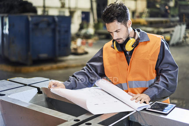 Man wearing protective workwear looking at blueprint in factory — Stock Photo
