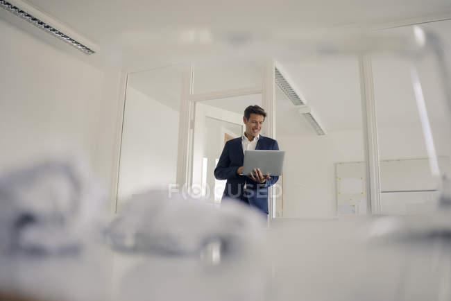 Homme d'affaires debout dans le bureau, en utilisant un ordinateur portable — Photo de stock