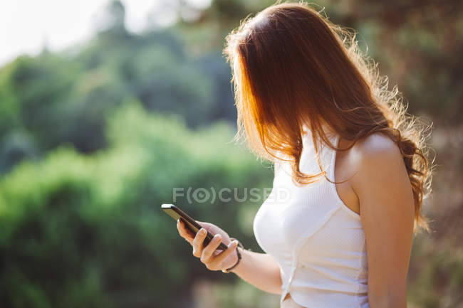 Unrecognizable redheaded woman using cell phone outdoors — Stock Photo