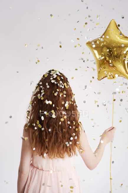 Vista posteriore di giovane donna rossa con palloncino dorato a forma di stella sotto la doccia di coriandoli — Foto stock
