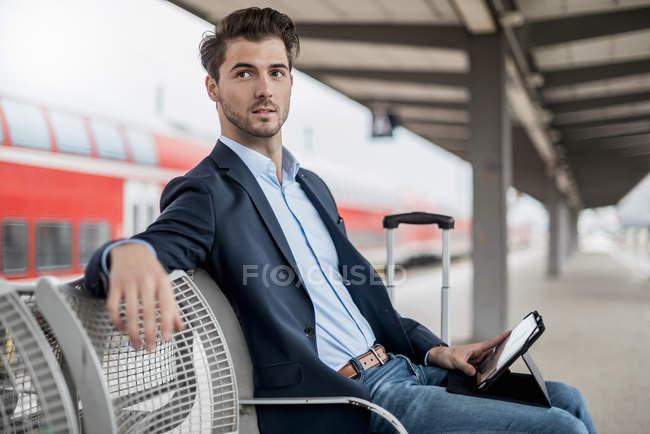 Бизнесмен на станции с помощью планшета — стоковое фото