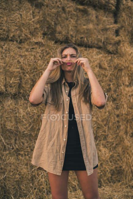 Jovem mulher de pé na frente de fardos de feno fazendo bigode com o cabelo — Fotografia de Stock