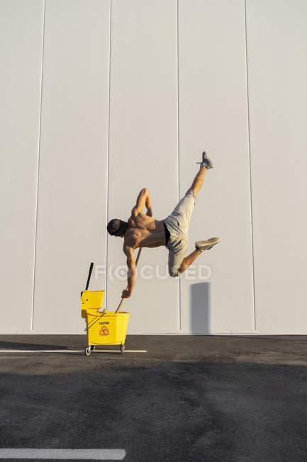 Акробат, играющий с моющими ковриками и шваброй — стоковое фото