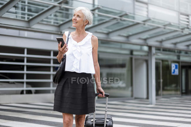 Улыбающаяся пожилая женщина с мобильным телефоном и багажом на ходу в городе — стоковое фото