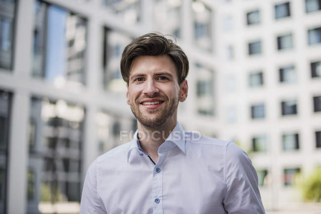 Portrait of smiling businessman walking in city — Stock Photo