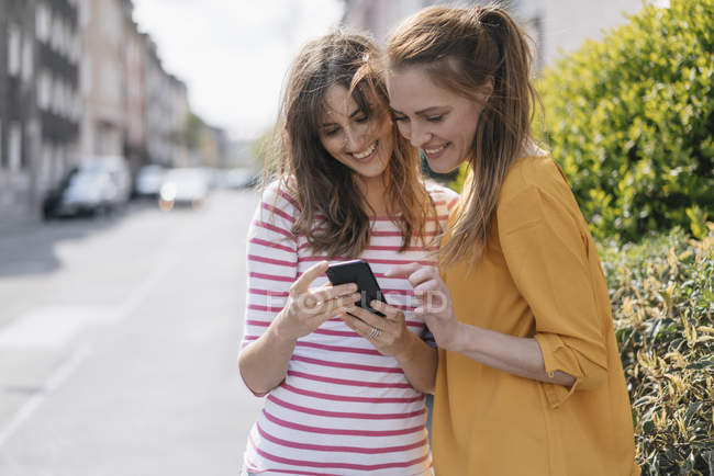 Female friends in city sharing smartphone — Stock Photo