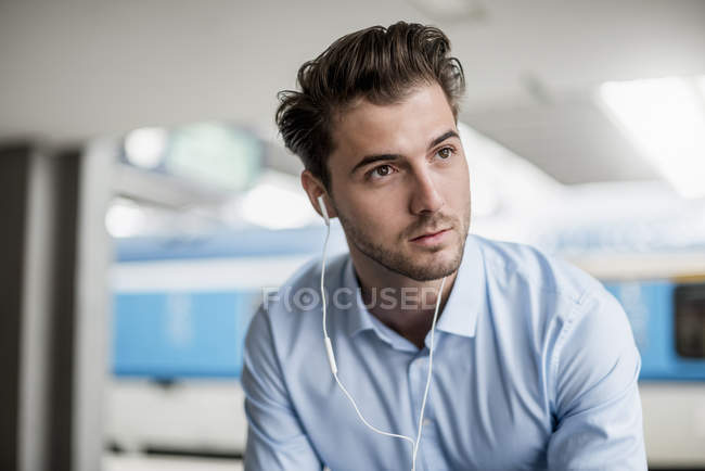 Portrait of businessman wearing earbuds at the station — Stock Photo
