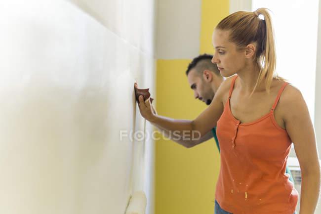 Молодая женщина и ее партнер шлифовальные стены в новом доме — стоковое фото