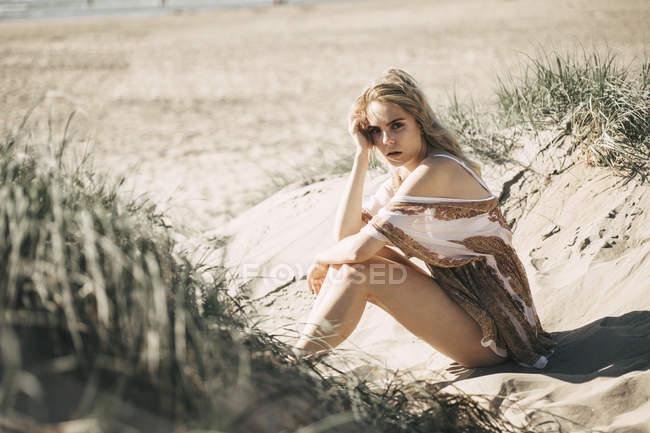 Retrato de uma jovem mulher sentada na duna de praia e olhando para a câmera — Fotografia de Stock