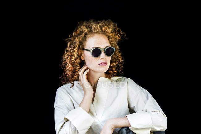 Portrait of stylish young woman with curly red hair wearing sunglasses in front of black background — Stock Photo