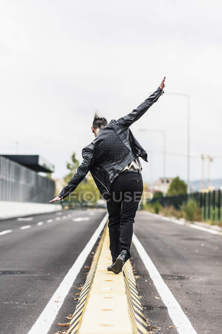 Rear view of punk woman balancing on barrier at roadside with outstretched arms — Stock Photo