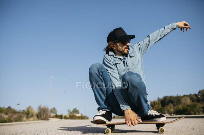 Trendy man in denim and cap skateboarding on street — Stock Photo
