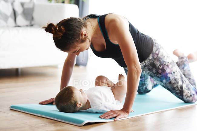 Мама с ребенком упражнения на коврик для йоги дома — стоковое фото