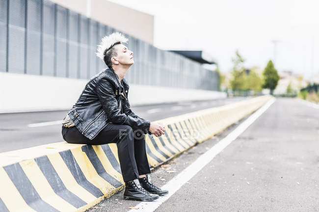 Punk woman sitting at roadside with closed eyes — Stock Photo